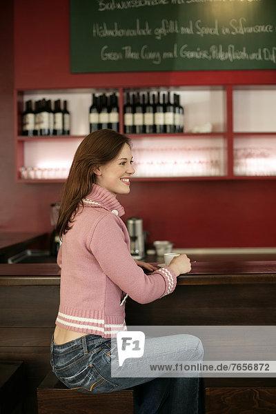 Frau sitzt am Tresen mit einem Espresso