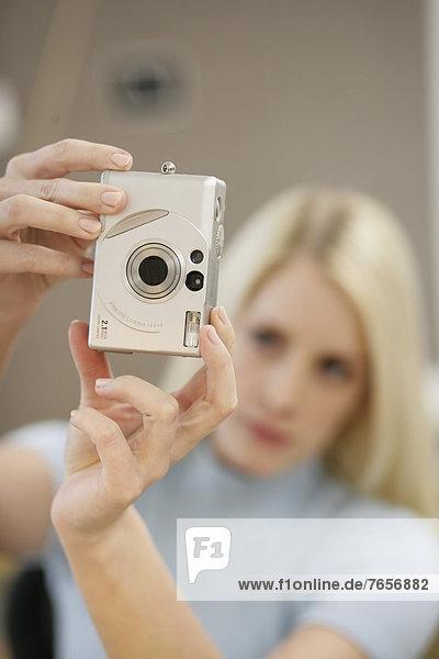 Frau fotografiert mit einer Digitalkamera