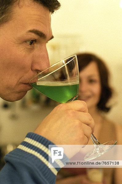 Mann trinkt grünen Likör - Alkoholische Getränke - Feier
