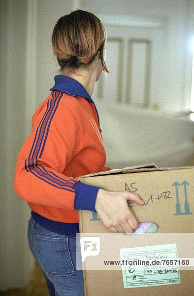 Junge Frau trägt Umzugskarton - Wohnung - Umzug