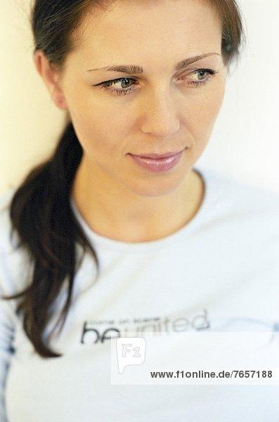 Portrait einer brünetten Frau mittleren Alters mit bedrucktem Oberteil