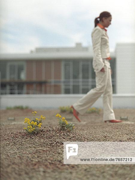 Junge Frau in hellem Kostüm geht spazieren