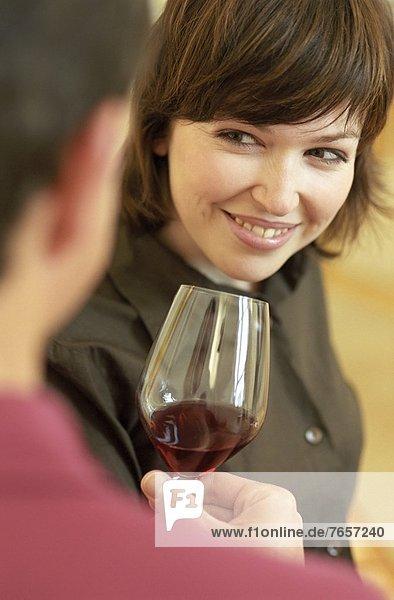 Mann hält einer brünetten Frau ein Glas Wein hin - Blick - Alkohol - Flirt