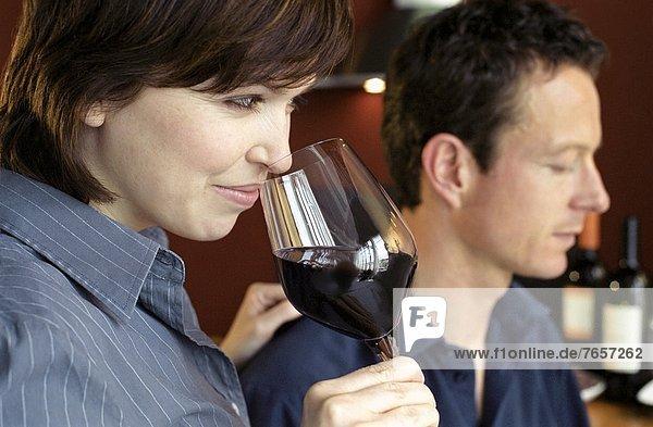 Mann und Frau mittleren Alters riechen an Weingläsern - Probieren - Genuss - Alkohol