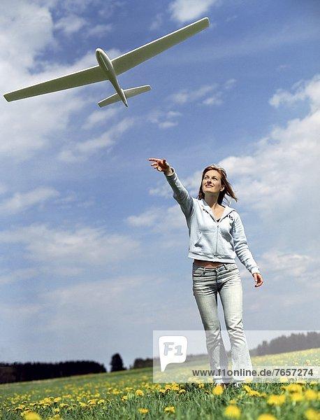 Frau mittleren Alters lässt ein Modell-Segelflugzeug fliegen - Schwung - Freizeit - Sommer - Wiese