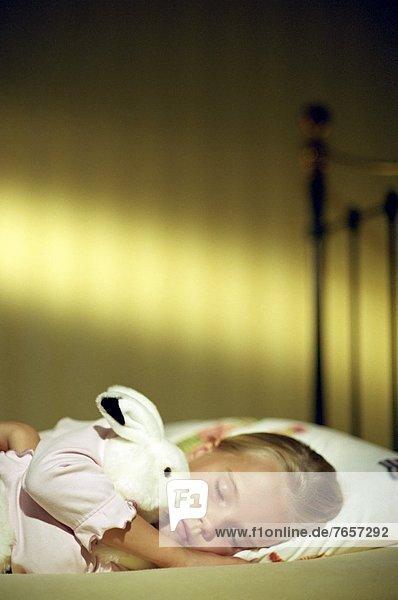 Kleines blondes Mädchen mit einem Stoffhasen im Arm - Kuscheltier - Kindheit - Einschlafen