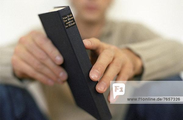 Mann hält Buch in der Hand (Nahaufnahme)