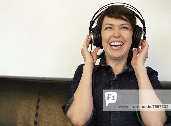 Junge  dunkelhaarige  lachende Frau hört Musik über einen Kopfhörer