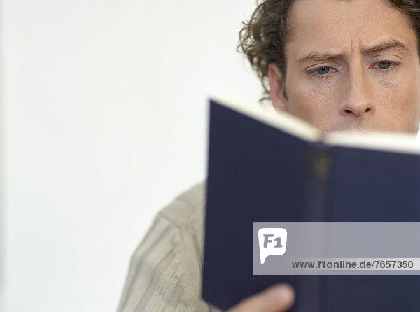 Mann liest in einem schwarzen Buch