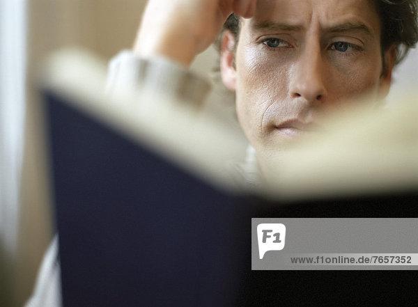 Mann liest in einem schwarzen Buch (Nahaufnahme)