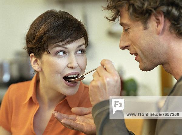 Mann füttert Frau mit einem Löffel - Pärchen