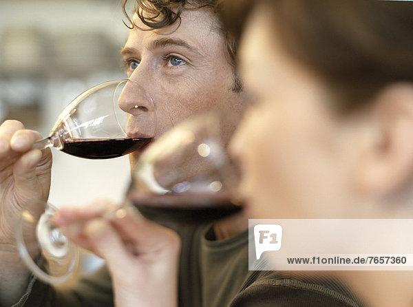 Mann und Frau trinken Rotwein (Profil) - Pärchen beim Kochen