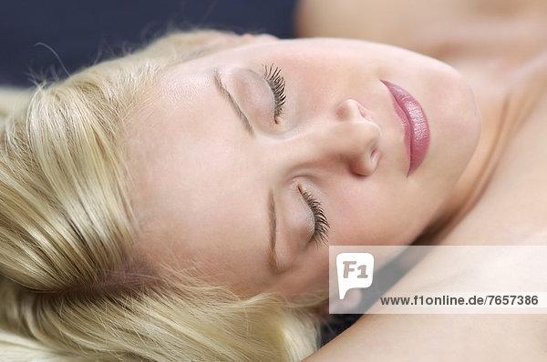 Junge Frau mit langen blonden Haaren hält ihre Augen genießend geschlossen - Erotik