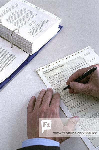 Alter Mann füllt Antrag aus - Arbeitsamt