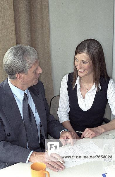 älterer Mann und junge Frau bei einer Teambesprechung - Arbeitsplatz - Büro