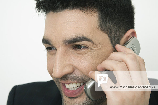 Mid-adult businessman talking on cell phone  smiling