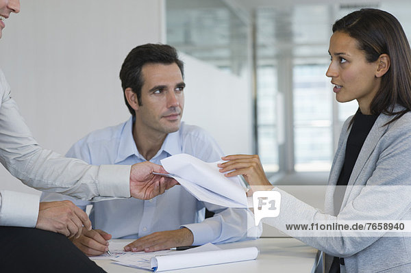 Colleagues discussing documents in meeting
