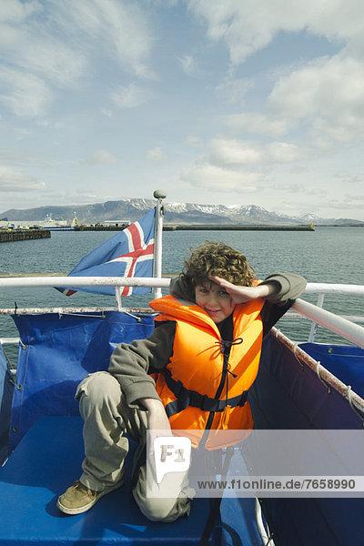 Junge in einer Schwimmweste auf einem Boot,  Reykjavik Island