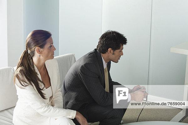 Businesswoman watching businessman playing video game