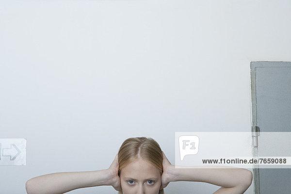 Junge Frau mit den Händen über den Ohren