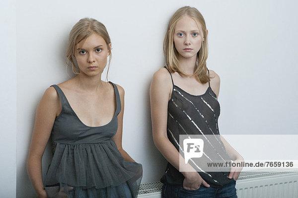 Teenagermädchen und junge Frau an der Wand lehnend  Portrait