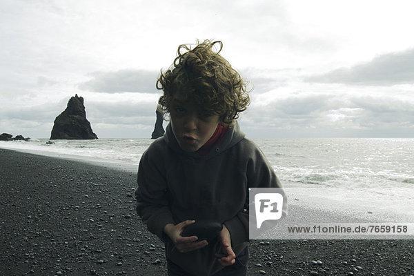 Grimassierender Junge am Strand von Island