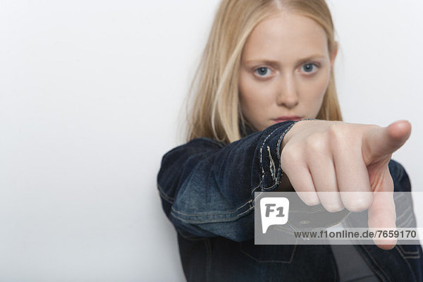 Junge Frau  die mit dem Finger anklagend zeigt