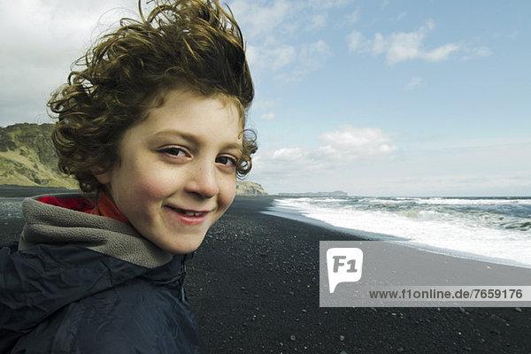 Portrait eines lächelnden Jungen am Strand,  Island