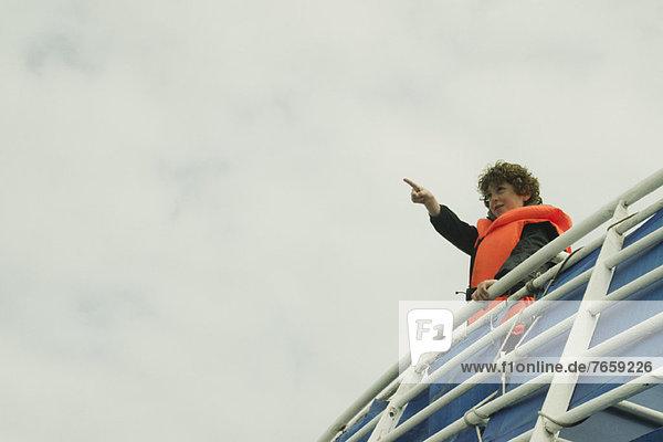 Junge,  der den Horizont beobachtet,  auf dem Oberdeck eines Bootes.