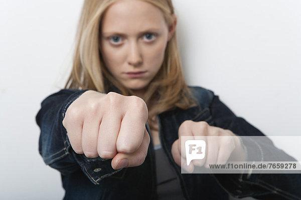 Junge Frau mit geballten Fäusten