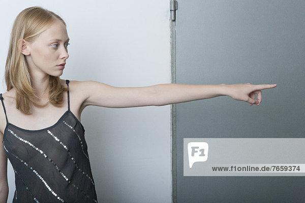 Junge Frau zeigt und schaut weg.