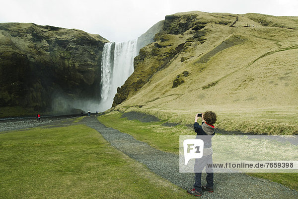 Junge fotografiert einen Wasserfall  Island