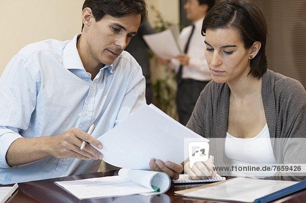 Kollegen besprechen Dokument im Büro