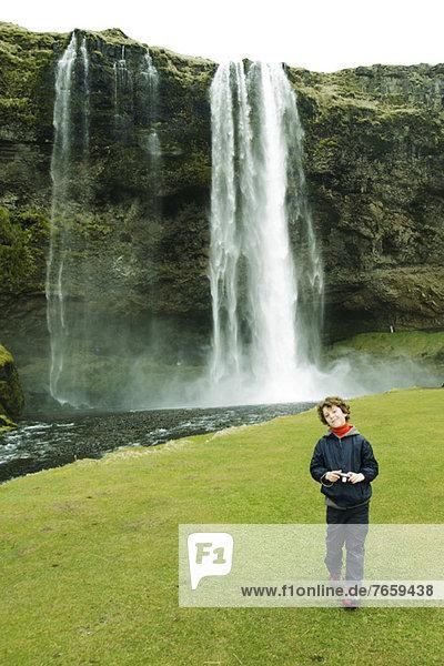 Lächelnder Junge posiert vor einem Wasserfall,  Island