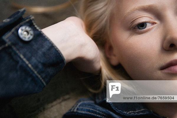 Junge Frau im Liegen mit den Händen hinter dem Kopf  Portrait