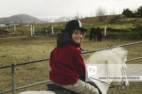Lächelnder Junge auf einem Islandpferd  Island