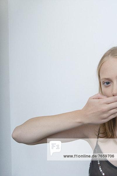 Junge Frau  die den Mund mit der Hand bedeckt