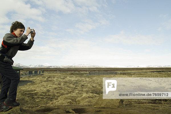 Junge fotografiert die Gullfoss-Landschaft  Island
