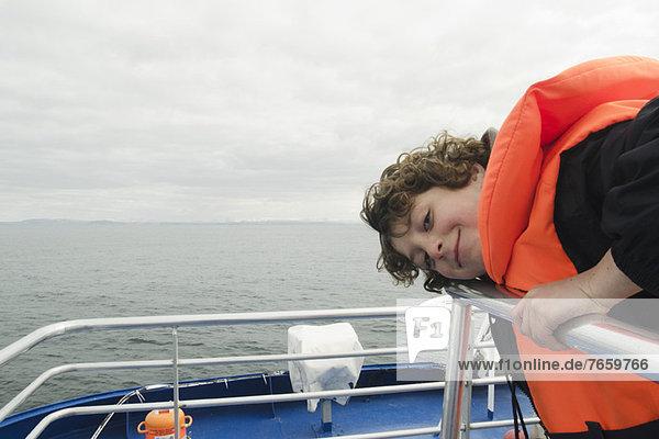 Junge  der sich an Deck eines Bootes lehnt  lächelnd