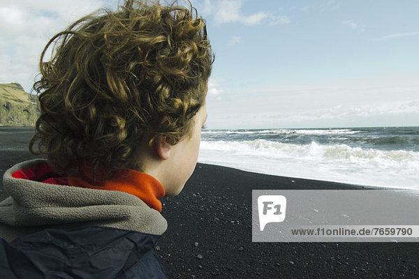 Junge mit Blick auf das Meer,  Island