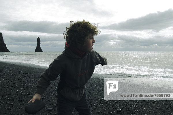Junge,  der am Strand abprallt Island