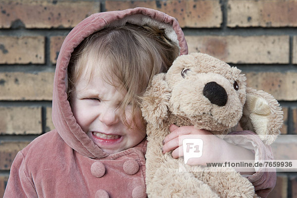 Kleines Mädchen umarmt ausgestopften Hund,  Portrait