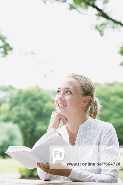 Junge Frau beim Lesen im Park