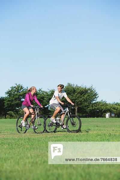Couple riding mountain bikes in a park