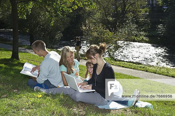 Studenten mit Laptop und Buch auf einer Wiese  Freiburg im Breisgau  Baden-Württemberg  Deutschland  Europa
