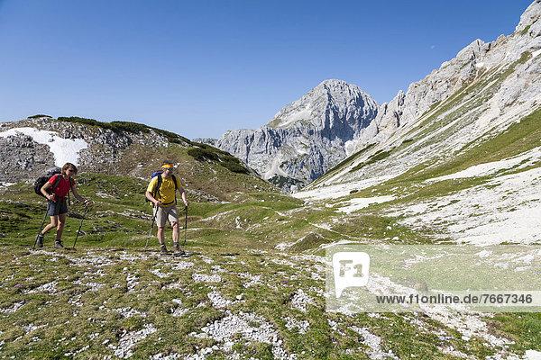 Ein Mann und eine Frau beim Wandern  Aufstieg von der Berghütte Vodnikov dom zum Triglav  Nationalpark Triglav  Slowenien  Europa