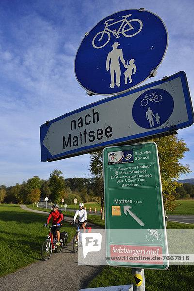Elektro-Radfahrer vor Schild mit Radwegen  Fraham  Grabensee  Salzburger Seenland  Salzburg  Österreich  Europa