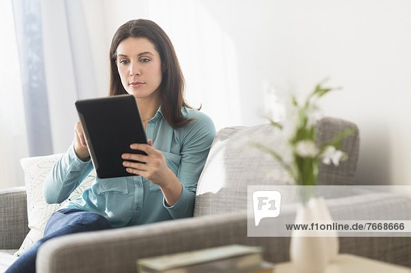 Woman using digital tablet while sitting on sofa