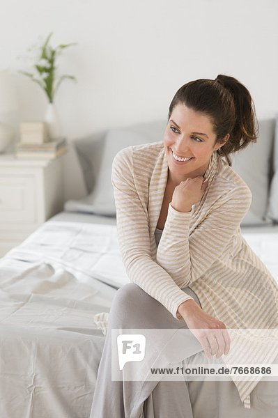 Frau sitzt auf dem Bett