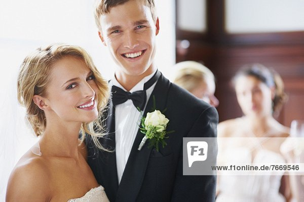 Portrait of newly wed couple  bridesmaids in background